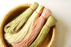 Spaghetti chinois colorés sur le panier en bambou à l'arrière-plan blanc photos stock