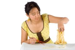 Spaghetti and chopsticks. Chinese woman eating noodles with hands and chopsticks Stock Photography
