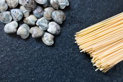spaghetti and clams on a black granite table, ingredients of Ita stock photos