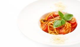 Spaghetti classici con i pomodori ciliegia ed il parmigiano decorati con basilico sul piatto bianco fotografia stock