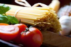 Spaghetti close up. Raw pasta with tomato, basill and garlic close up Royalty Free Stock Images
