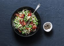 Spaghetti con bacon ed i piselli cremosi su un fondo scuro fotografia stock libera da diritti