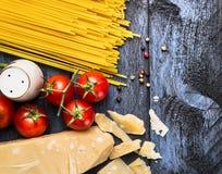 Spaghetti con i pomodori ed il parmigiano su fondo di legno blu, vista superiore Fotografia Stock