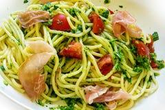 Spaghetti con il pesto, il prosciutto di Parma ed i pomodori verdi Fotografie Stock Libere da Diritti