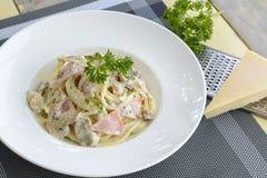 Spaghetti con la crema del fungo e del prosciutto Fotografie Stock
