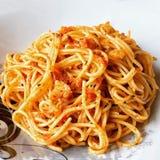 Spaghetti con la salsa rossa di pesto e la carne di maiale croccante fotografie stock libere da diritti