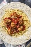 Spaghetti con le polpette deliziose fatte da carne tritata in una salsa al pomodoro piccante in un piatto con la pasta dell'iscri fotografia stock