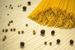 Spaghetti crudi e spezie sulla tavola fotografie stock libere da diritti