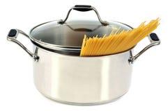 Spaghetti crudi in un forno olandese su un fondo bianco fotografie stock libere da diritti