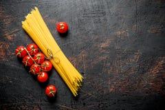 Spaghetti crus avec des tomates sur une branche photo stock