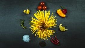 Spaghetti crus entourés par des ingrédients de pâtes photo libre de droits