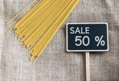 Spaghetti crus et vente dessin de 50 pour cent sur le tableau noir Photo libre de droits