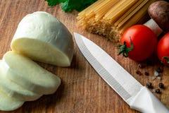 Spaghetti crus sur un conseil en bois avec du mozzarella, les légumes frais, les épices et les champignons coupés en tranches photos stock
