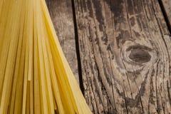Spaghetti crus sur une table en bois Photo libre de droits