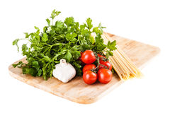 Spaghetti on a cutting board. A bunch of spaghetti, some cherry tomatoes, parsley and garlic on a cutting board isolated over a white background Royalty Free Stock Photo