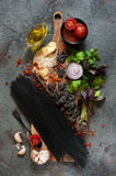 Spaghetti with cuttlefish ink, farfalle pasta and ingredients. Royalty Free Stock Photos