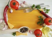 Spaghetti czosnku pieprz, olej, nóż, rozwidlenie na białym drewnianym tle Zdjęcie Stock