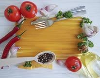 Spaghetti czosnku ramowy pieprz, olej, tradycyjny, rozwidlenie na białym drewnianym tle Fotografia Stock