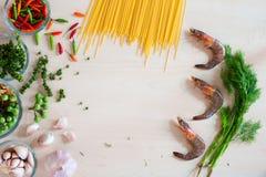 Spaghetti d'ingrédient avec des crevettes et de fines herbes sur le fond blanc Images stock