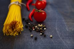 Raw pasta,tomatoes and chili. Spaghetti on a dark wooden background. Raw pasta,tomatoes and chili close-up Royalty Free Stock Photography