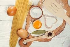 Spaghetti de pâtes avec de la farine, oeuf sur le fond en bois rustique Photographie stock libre de droits