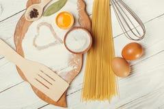 Spaghetti de pâtes avec de la farine, oeuf sur le fond en bois rustique Images libres de droits