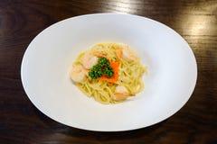 Spaghetti deliziosi con i gamberetti e tobiko su un piatto su un legno Immagine Stock