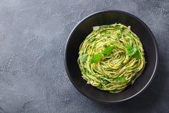 Spaghetti della pasta con la salsa di pesto in ciotola nera Fondo grigio Copi lo spazio Vista superiore immagini stock