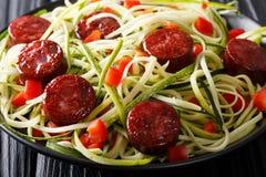 Spaghetti dello zucchini con pepe ed il primo piano fritto della salsiccia Horiz immagini stock libere da diritti
