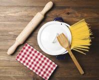 Spaghetti dentro un vaso accanto ad una forcella di legno e un rullo sulla tavola di legno Fotografia Stock