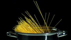 Spaghetti die in pot op zwarte achtergrond vallen stock footage