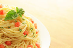 Spaghetti dish with copy space. Sideways shot of a vegetarian spaghetti dish with dry spaghetti in the background Royalty Free Stock Images