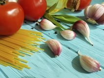 Spaghetti dried tomato garlic, pepper, oil nutrition a blue wooden background Royalty Free Stock Photos