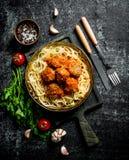 Spaghetti e polpette in pentola con le spezie, le erbe ed i pomodori fotografia stock