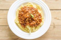 Spaghetti e salsa rossa su un piatto bianco su una tavola di legno Fotografia Stock Libera da Diritti