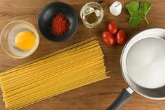 Spaghetti ed uova con la spezia sul fondo di legno della tavola per il cooki Fotografie Stock