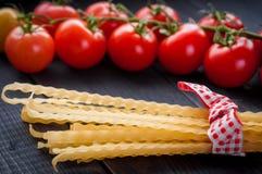Spaghetti et tomates italiens de pâtes avec des herbes sur une table en bois Photos stock