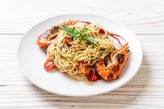 spaghetti faits sauter à feu vif avec les crevettes et les tomates grillées photo libre de droits
