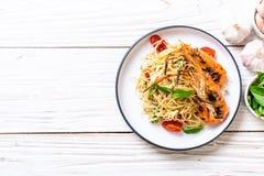 spaghetti faits sauter à feu vif avec les crevettes et les tomates grillées photographie stock
