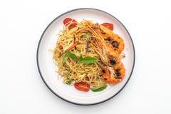 spaghetti faits sauter à feu vif avec les crevettes et les tomates grillées image libre de droits