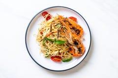 spaghetti faits sauter à feu vif avec les crevettes et les tomates grillées images libres de droits
