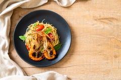 spaghetti faits sauter à feu vif avec les crevettes et les tomates grillées images stock