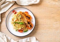 spaghetti faits sauter à feu vif avec les crevettes et les tomates grillées photos stock