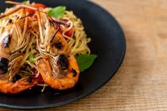 spaghetti faits sauter à feu vif avec les crevettes et les tomates grillées photo stock