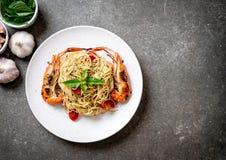 spaghetti faits sauter à feu vif avec les crevettes et les tomates grillées photographie stock libre de droits