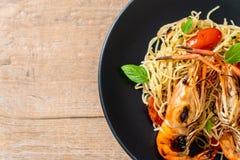 spaghetti faits sauter à feu vif avec les crevettes et les tomates grillées image stock