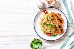 spaghetti faits sauter à feu vif avec les crevettes et les tomates grillées photos libres de droits