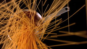 Spaghetti falling in a pot on black background. In slow motion stock video footage