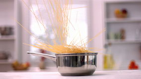 Spaghetti falling in a pot in kitchen stock footage