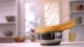 Spaghetti falling in pot in kitchen. In slow motion stock video